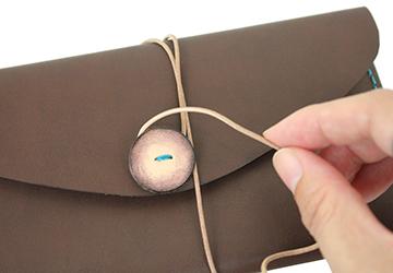 22色からステッチが選べる 手縫いレザーケース(牛革/日本製)革紐をボタン部分に巻きつけてとめます。